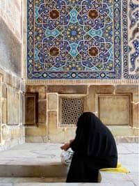 Source: http://www.flickr.com/photos/hamed/196805560/ Title: woman in black chador prays on steps of mosque, blue tiled decorations in background